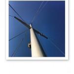 En segelbåtsmast med stag, mot en klarblå sommarhimmel.