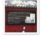 """Skylt som säger """"Välkommen till Grinda"""" på en rödmålad husfasad."""