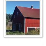 En röd ladugård i solen, mot blå himmel och grönt gräs.