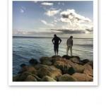Silhuetter av två män mot blått vatten och blå himmel, ståendes på ett par stenar.