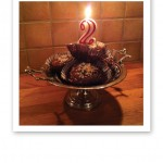Muffins med ett tänt 2-årsljus.