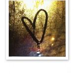 Ett hjärta ritat i imma på ett fönster.