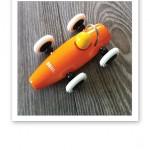 En gul-orange leksaksbil från Brio, mot ett grått golv.