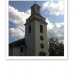 Kyrkan mot en blå sommarhimmel.