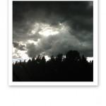 En olycksbådande himmel med mörka moln och solens strålar på andra sidan.
