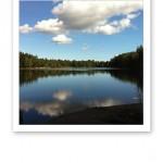 En blank sjö med speglingen av vita moln på en blå himmel.